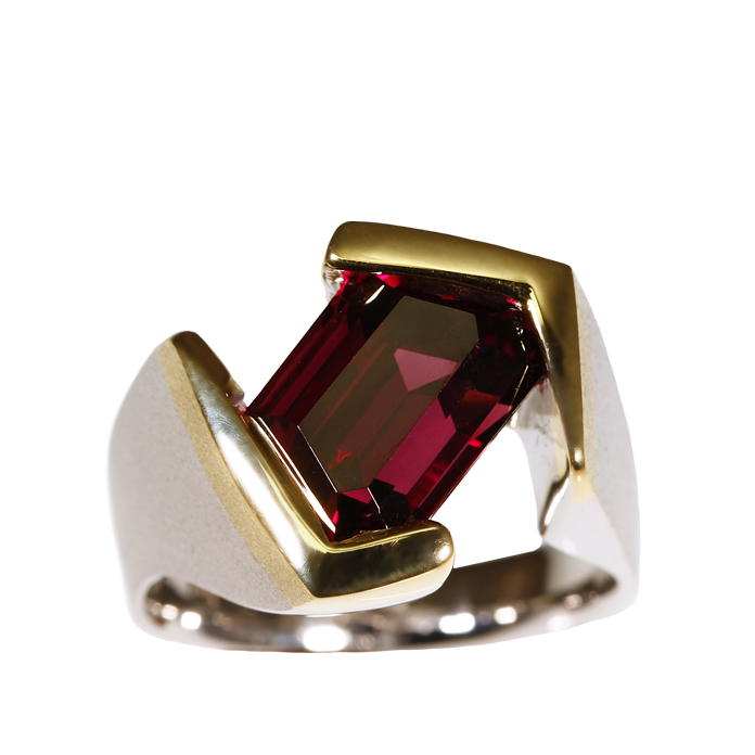 """""""Trapezoid Red"""" is one of the most architectural rings we have ever created. Our 18 karat yellow and 14 karat white gold setting holds a unique 9.91 trapezoid cut Rhodilite Garnet cut by Steven Moriarty."""