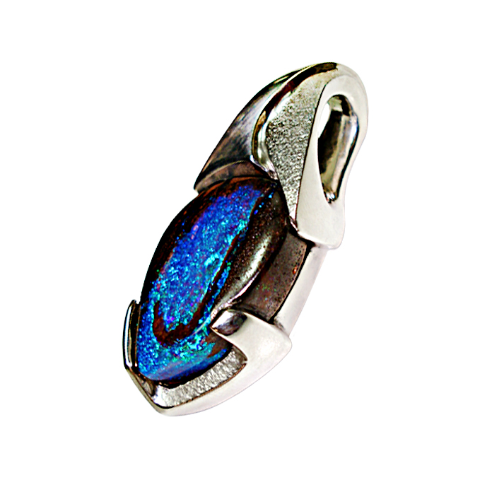 """Deep Sea Depths"" Pendant – This custom, one-of-a-kind pendant design features a unique channel and modified prong design with a modern flair. The sterling silver setting holds a hand-cut Australian Boulder Opal, measuring 30.13cts and 24x17x8.9 millimeters, in violet blue with blue and green pinfire play of color opal flash, seen from all angles. The setting has a ""sharkskin"" matte finish."