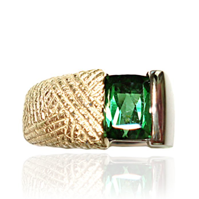 """Tut's Tourmaline"" Men's Ring - Showing off the warmth of Green Tourmaline this handcrafted gent's ring features an ""Egyptian"" finish on it 18 karat yellow gold side and a high polish luster on the 14 karat white gold side. The cushion cut 3.41 carat stone is set in an offset-channel design, suitable for daily wear or elegant celebrations. Luxurious and warm."