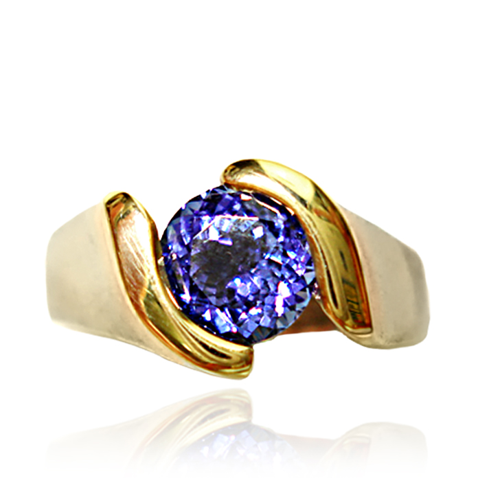 "Tanzanite ""Elegant Channel"" Ladies Ring - Set in 18 karat white gold with 14 karat yellow gold around the stone this 1.08 carat round Tanzanite is a show stopper for all blue lovers. The boldly engineered channel setting highlights the stone's violet-blue color while keeping it safe."