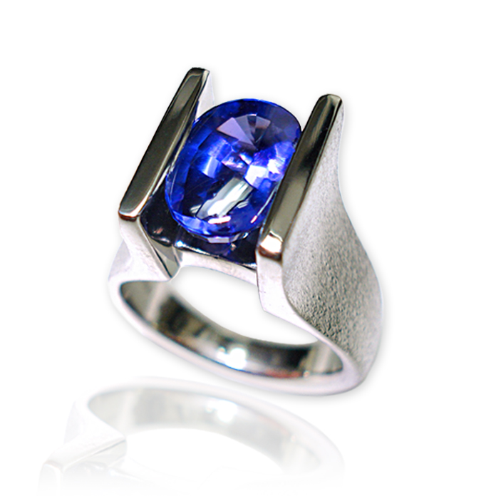 Straight Channel Tanzanite ladies ring — Buff top, oval deep blue Tanzanite, 3.12 carats, 11x7x5 millimeter, set in 14k white gold.